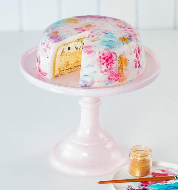 Fertige Aquarelltorte mit bunter Aquarelltechnik auf einer rosa Tortenplatte