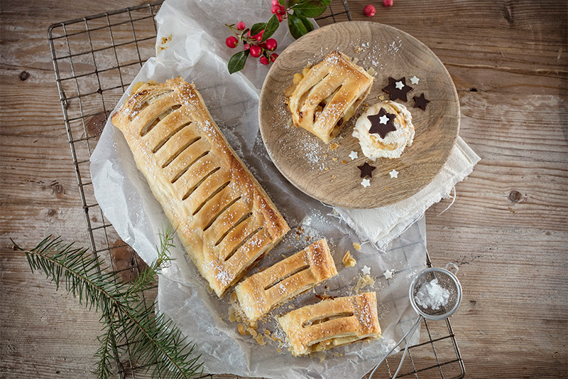 Apfelstrudel als Weihnachtskuchen neben Tannenzweigen dekoriert