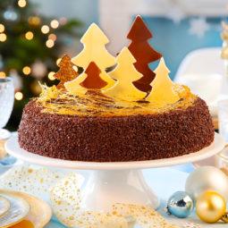 Weihnachtstorte mit Schnee aus Karamellfäden und dekoriert mit Tannenbäumen