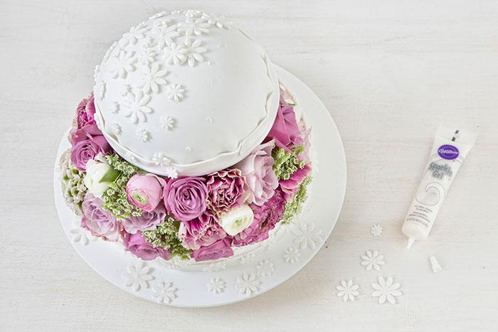 Auffällige Hochzeitstorte mit üppiger Blumendeko in Weiß und Pastell
