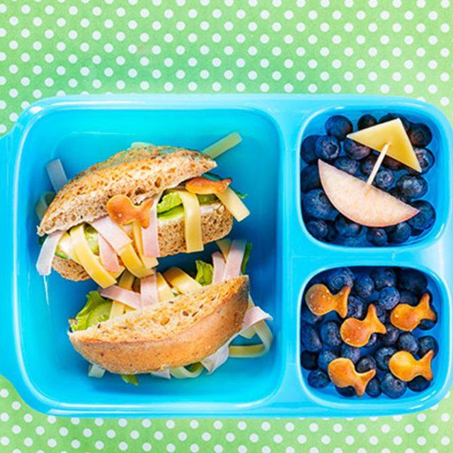 Bento Box gefüllt mit belegtem Brötchen und Blaubeeren