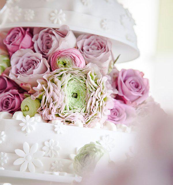 Blumendeko auf Hochzeitstorte in Kuppel-Optik in Weiß