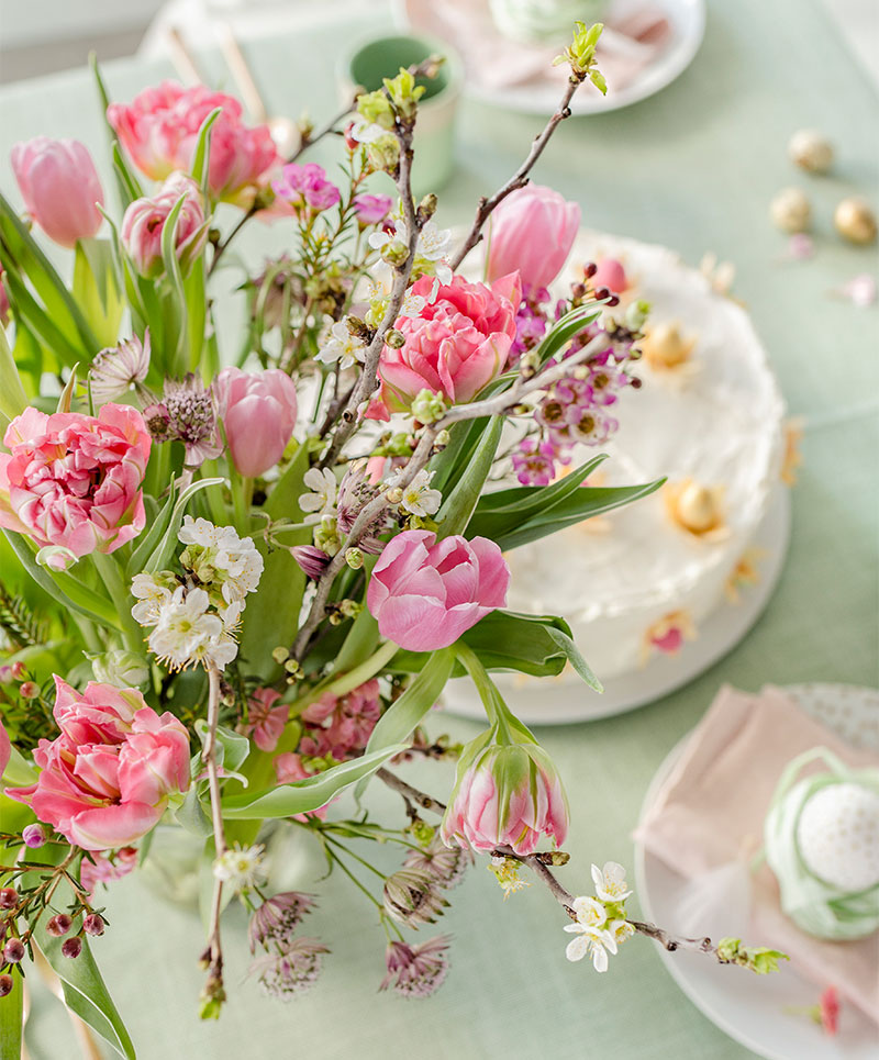Blumendeko passend arrangiert zur Torte zu Ostern