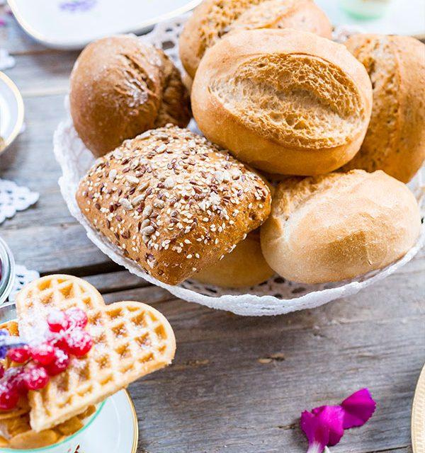 Brötchen auf festlich gedecktem Tisch mit Kuchen zum Muttertag