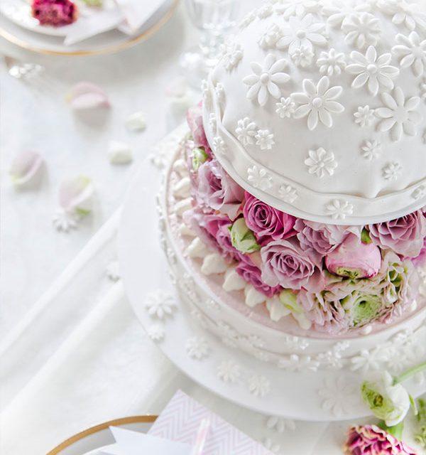 Dekorierter Tisch mit Hochzeitstorte als Kuppel mit vielen Blumen