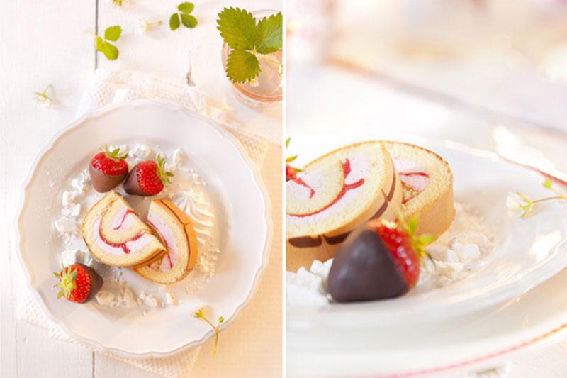 Erdbeerrolle aufgeschnitten mit Deko aus schokolierten Erdbeeren