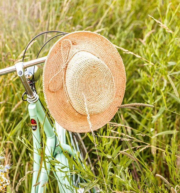 Fahrrad und Strohhut im Feld für die Radtour mit leckeren Snacks