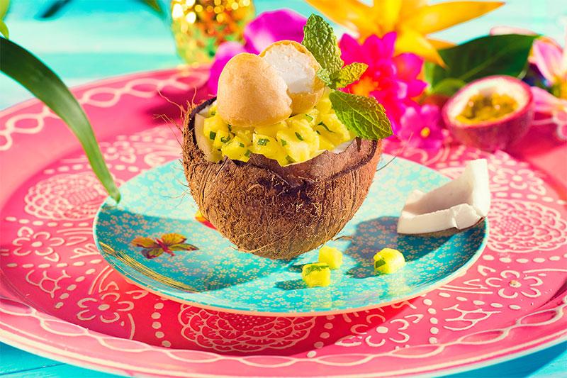 Kokosnuss dekoriert mit Windbeuteln und Minze