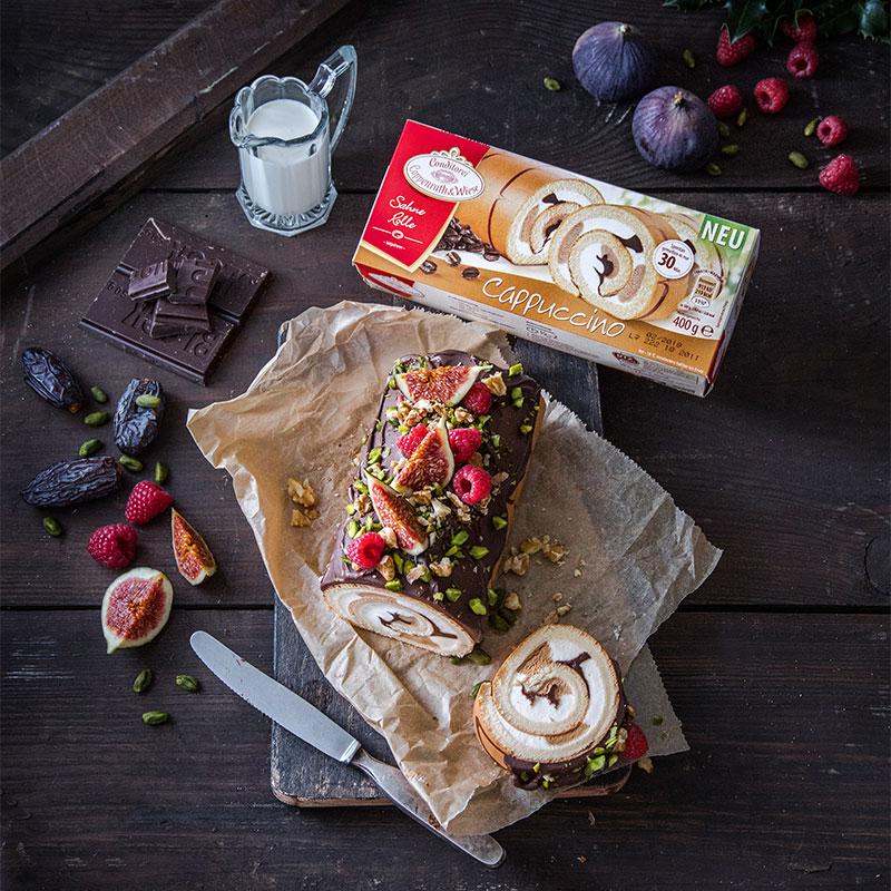 Kuchen Weihnachten Cappuccino-Sahne-Rolle mit Himbeeren und Dattel dekorieren