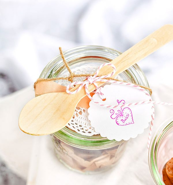 Leckere Mini-Kuchen im Glas mit Löffel und Deko