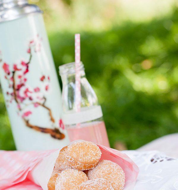 Mini-Berliner angerichtet in Papiertüte auf Picknicktisch