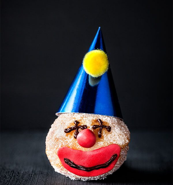 Mini-Berliner mit lustigem Clownsgesicht als Kuchen zu Karneval