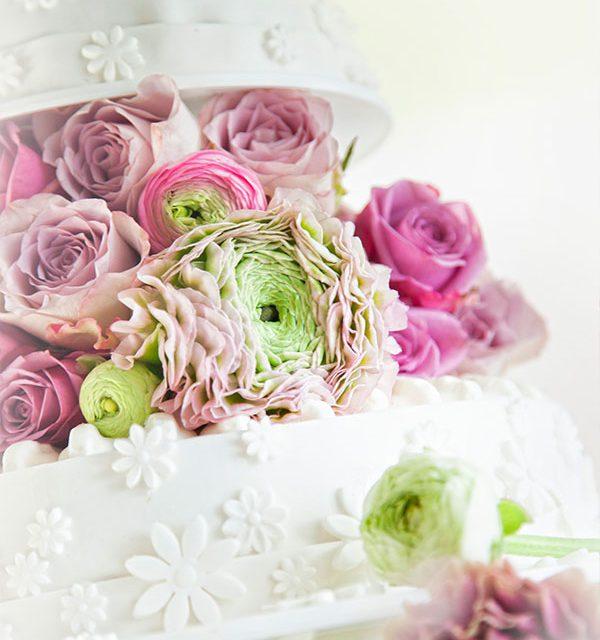 Mittig auf Hochzeitstorte platzierte Blumendeko zwischen den Kuppeln
