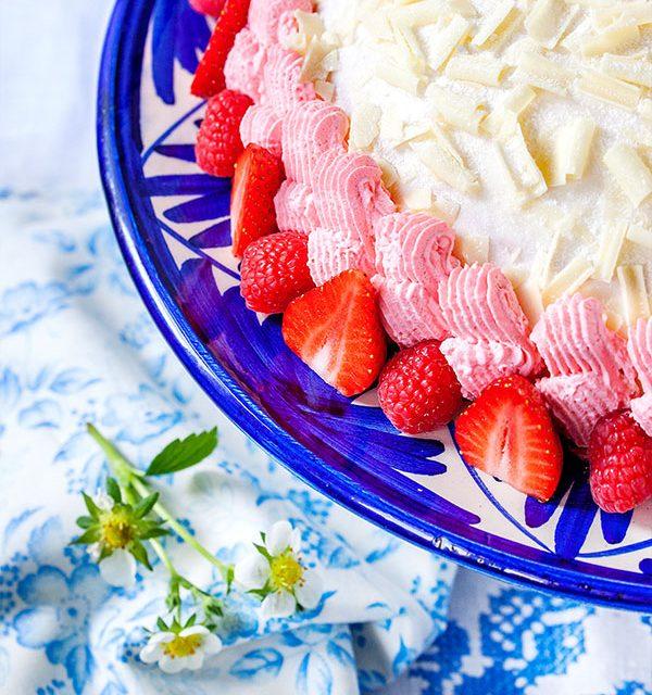 Rote Creme und frische Beeren an Sahnetorte mit weißer Schokolade