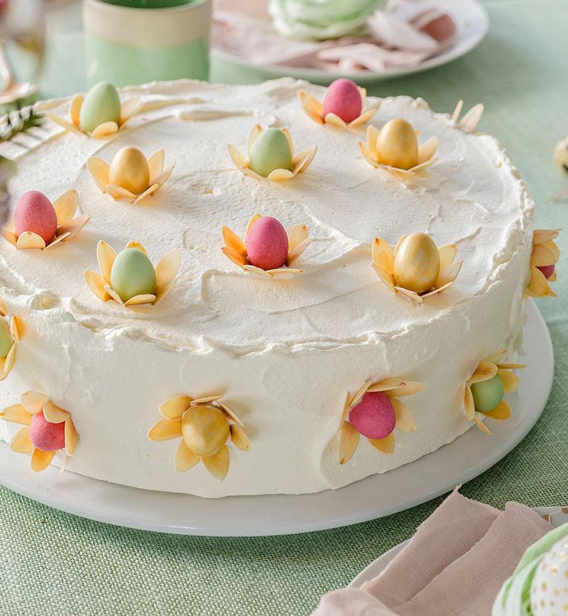 Torte zu Ostern dekoriert mit kleinen farbigen Ostereiern und Blüten