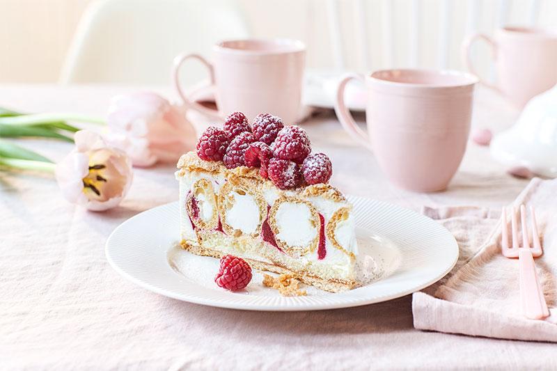 Tortenstück der Ostertorte dekoriert mit Himbeeren auf weißem Teller