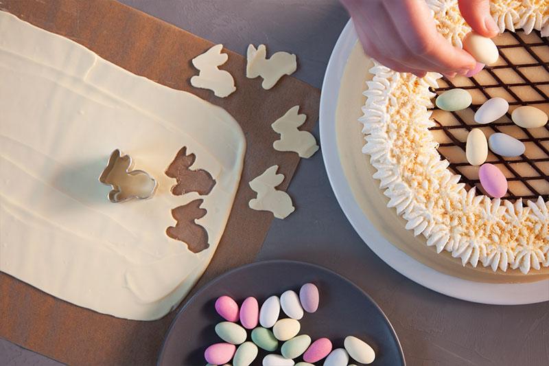 Zubereitung Torte für Ostern hübsch dekoriert mit farbigen Ostereiern